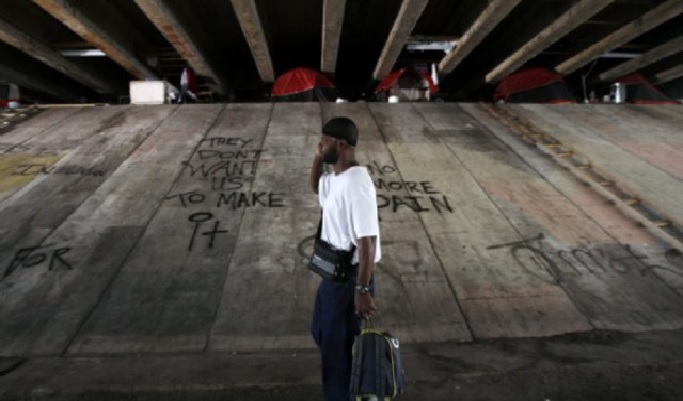 An afro-american man, a mobile phone to his ear and pulling a trolley, walks under the bridge at the Julia Tuttle Causeway. In the space between the bottom of the bridge and the top of its cement base, tents have been put in place. The ground is dirty and the cement covered in graffitis.